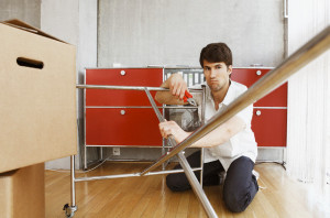 Young man assembling desk in apartment